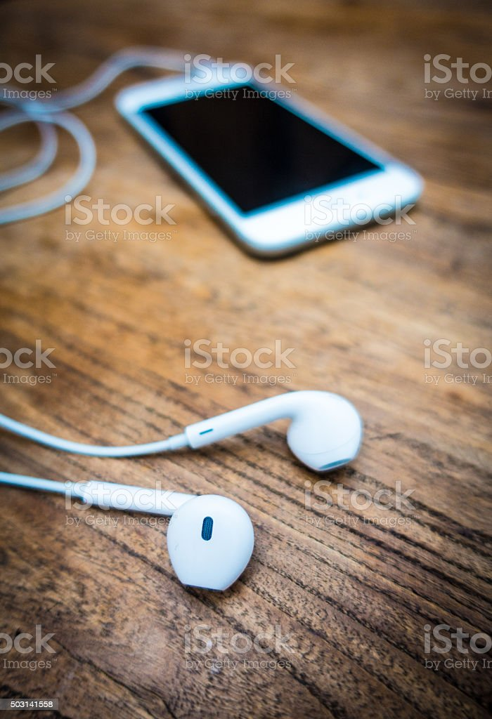 mobile phone and headphones lay on wooden table stock photo