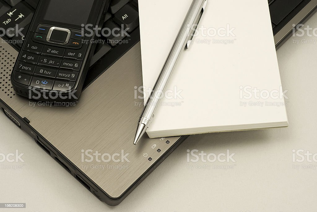 Mobile phone and notebook on a laptop royalty-free stock photo
