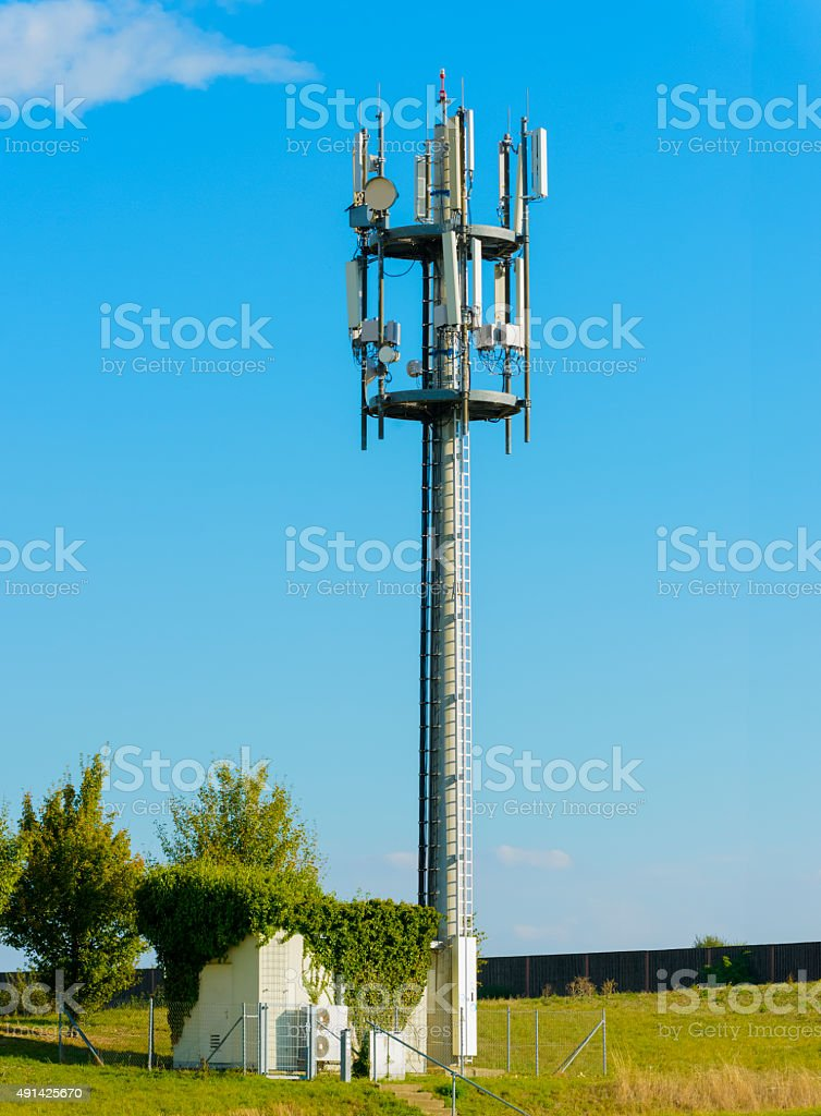 Mobile phone antenna base station ground field close blue sky stock photo