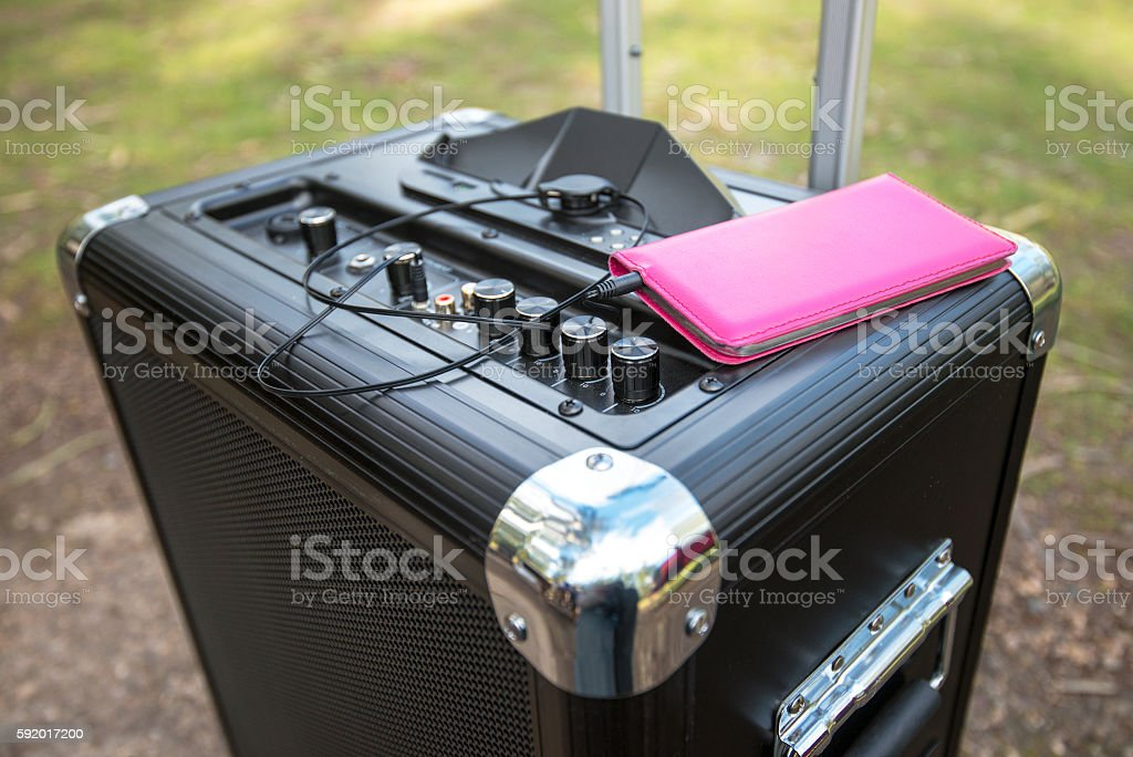 Mobile phone connected to portable PA sound system stock photo