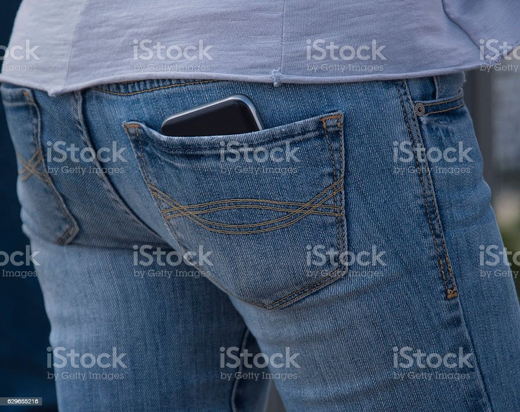 Mobile phone in a blue jeans pocket stock photo
