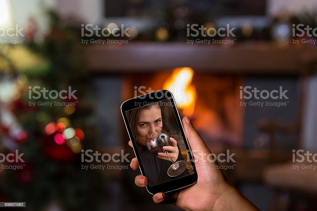 Mobile phone in hand showing selfie woman drinking red wine stock photo