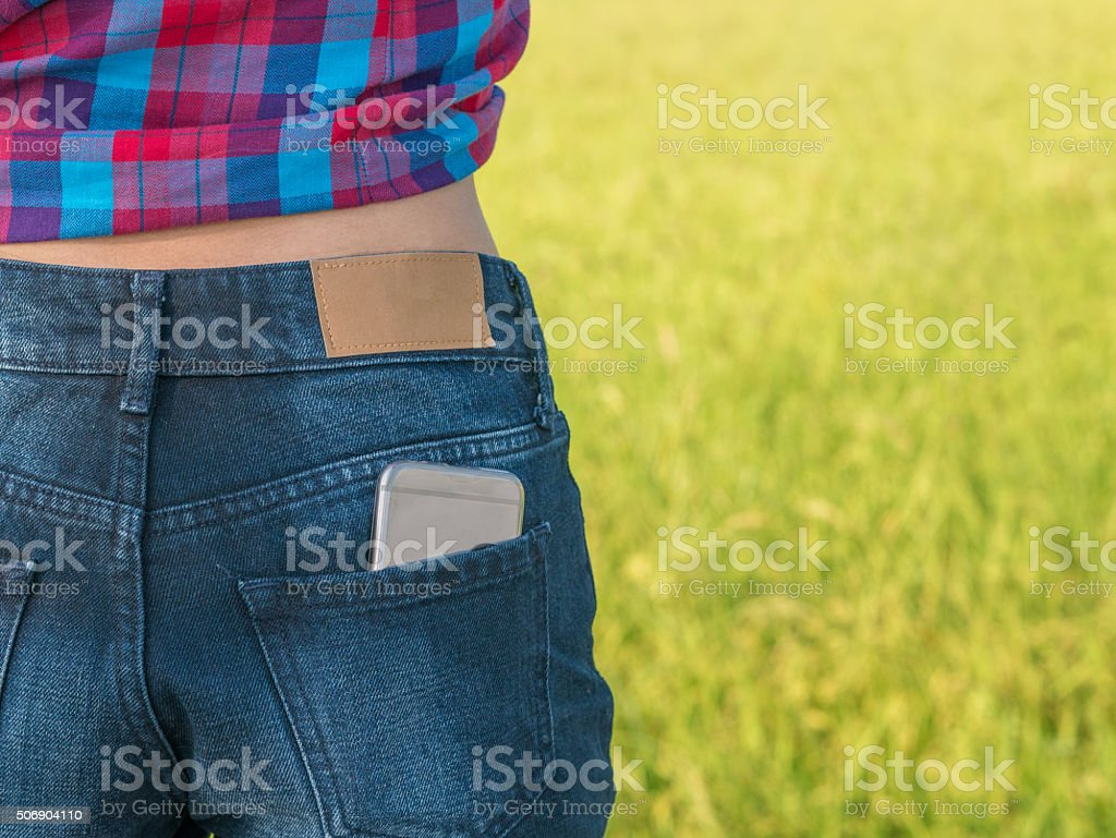 Mobile phone in pocket jean of girl outdoor royalty-free stock photo
