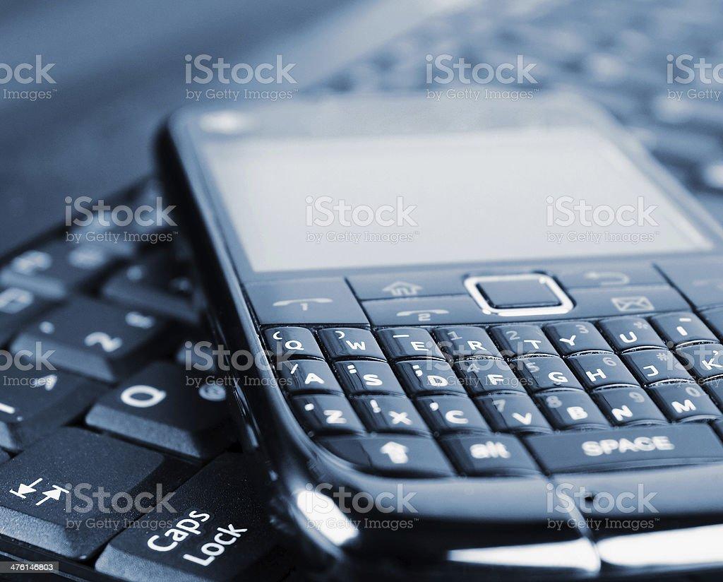 Mobile phone on laptop keyboard royalty-free stock photo