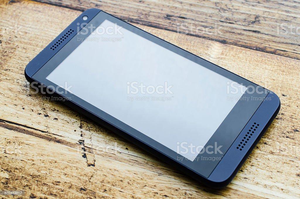 Mobile phone on wooden desk stock photo