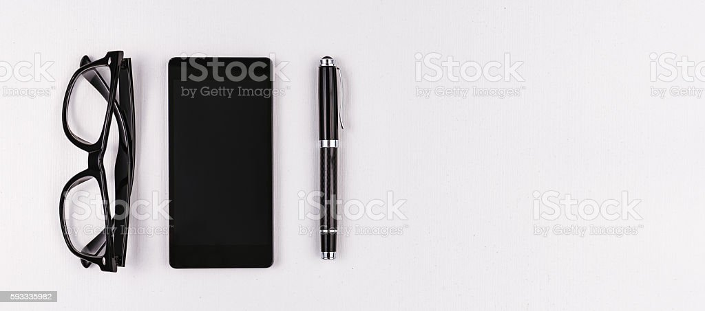 Mobile phone, pen and eyeglasses on white background stock photo