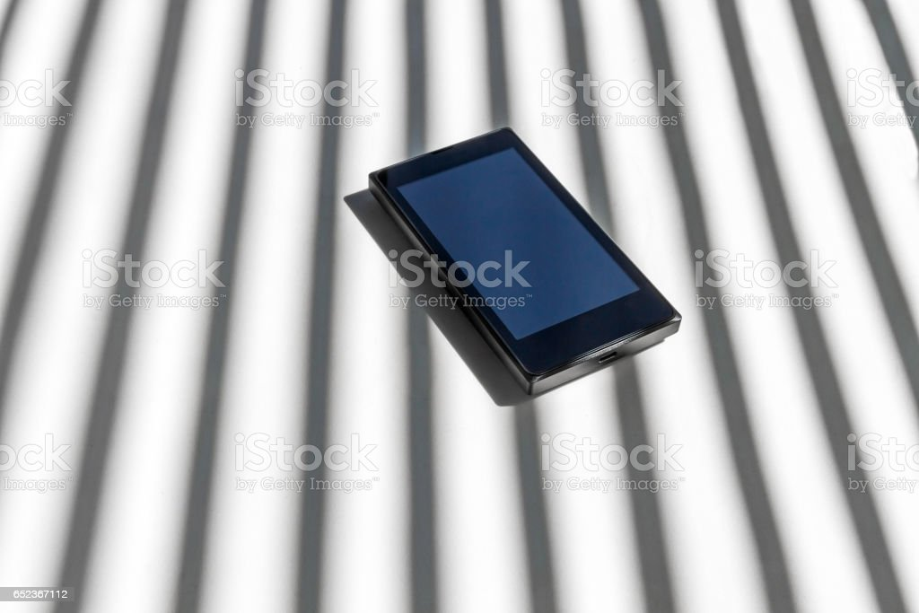 Mobile Phone Smartphone behind Bars Shadow - Telefono Movil Smartphone entre Barrotes de Sombra stock photo