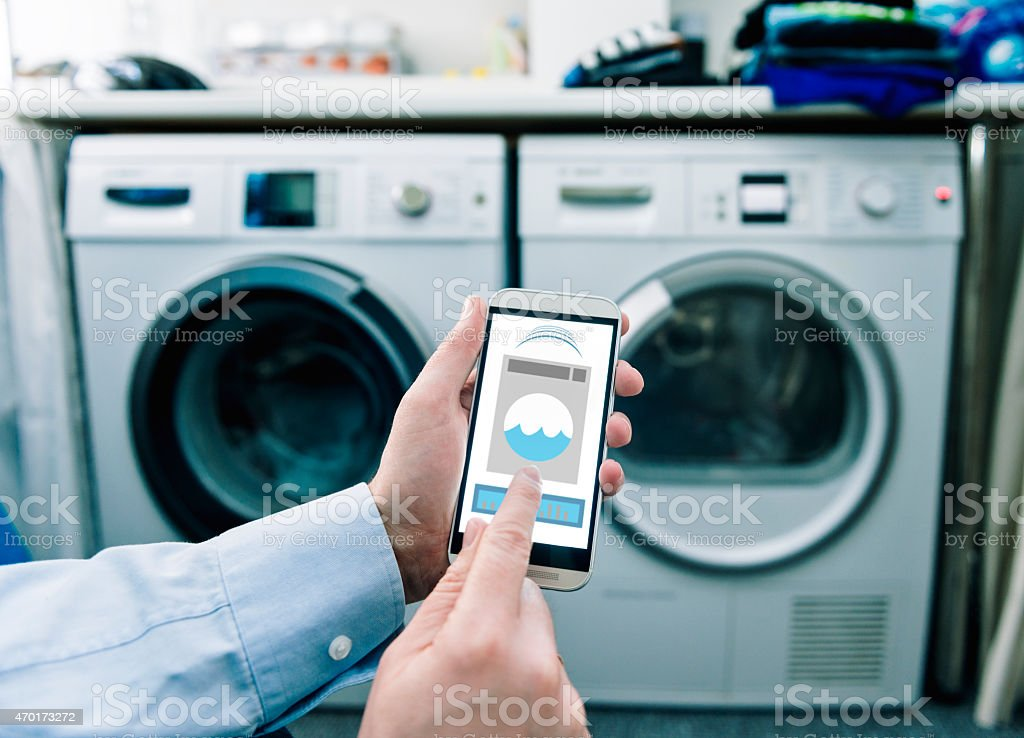 Mobile phone with app used to control washing machines stock photo