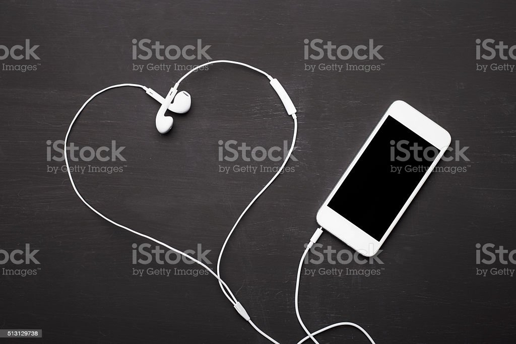 Mobile phone with headphones for music listening stock photo