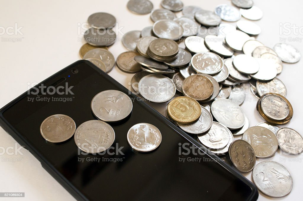 Mobile phone with Indian coins stock photo