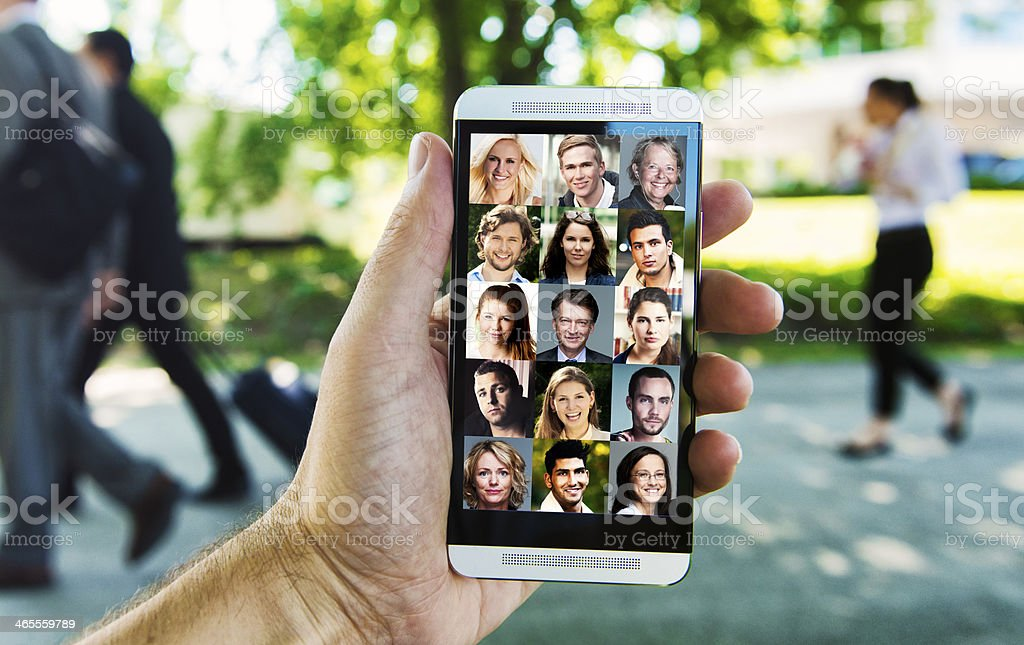 Concept of social networking with the mobile phone. Hand holds a...