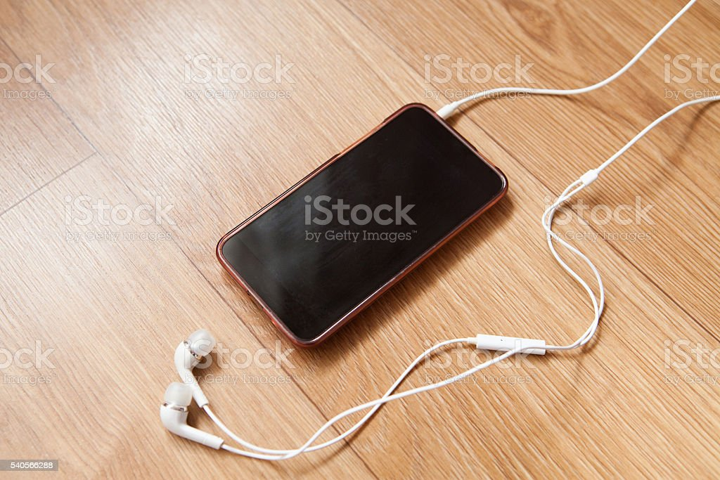 Mobile phone with white headphones stock photo