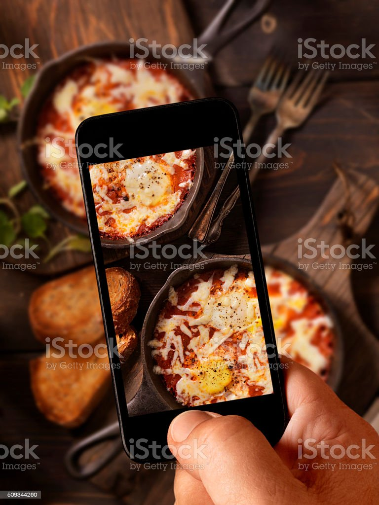 Mobile Photography of Eggs Baked in Spice Tomato Sauce stock photo