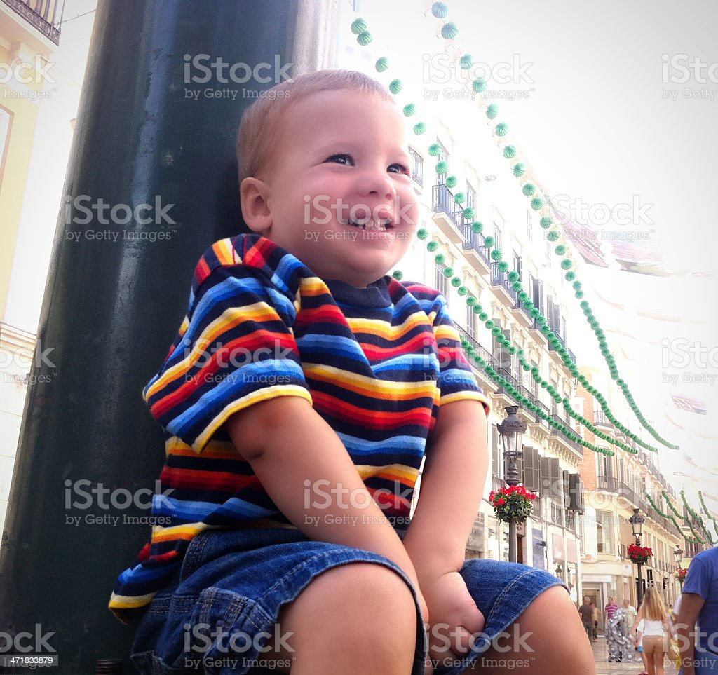 Mobile Stock - Boy Sitting in decorated city center stock photo