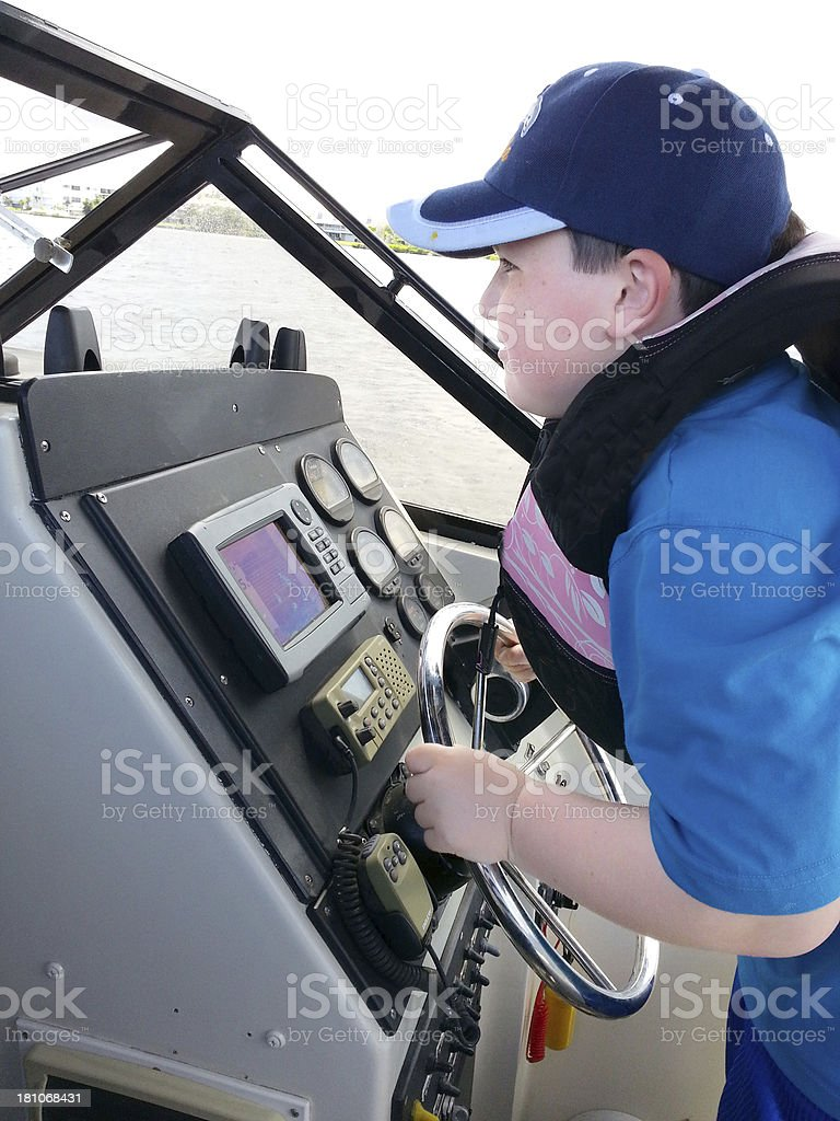 Mobile Stock - seven year old driving a boat royalty-free stock photo