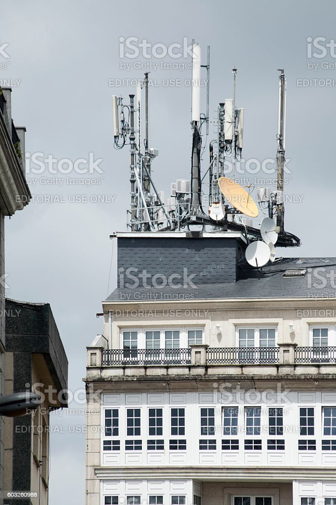 Mobile telephony and television relay antennas on residential building roof. stock photo