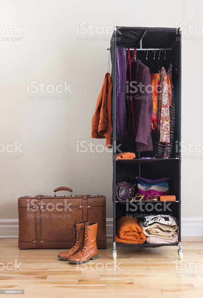 Mobile wardrobe with clothing and leather suitcase royalty-free stock photo