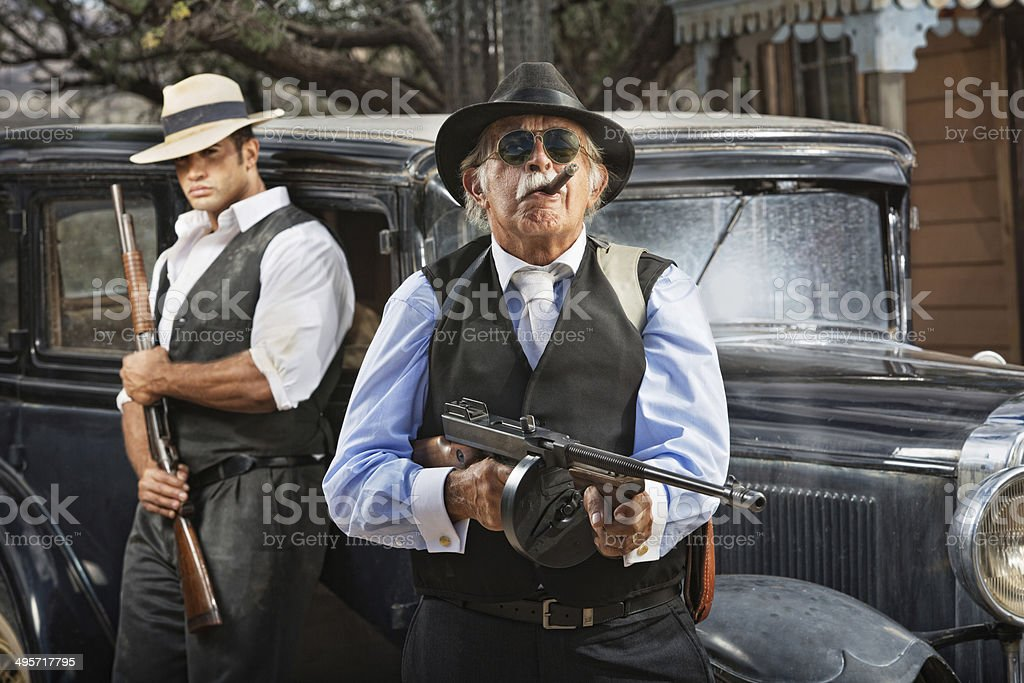Mobster boss and guard with guns near black car stock photo