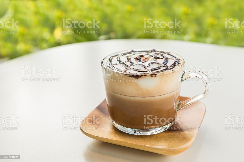 Mocha coffee with wooden saucer on white table. stock photo