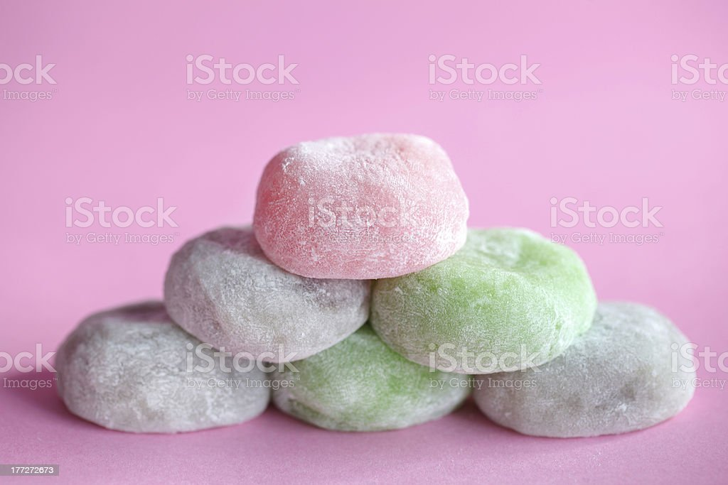 Mochi colorful japanese rice cakes stacked on pink background stock photo