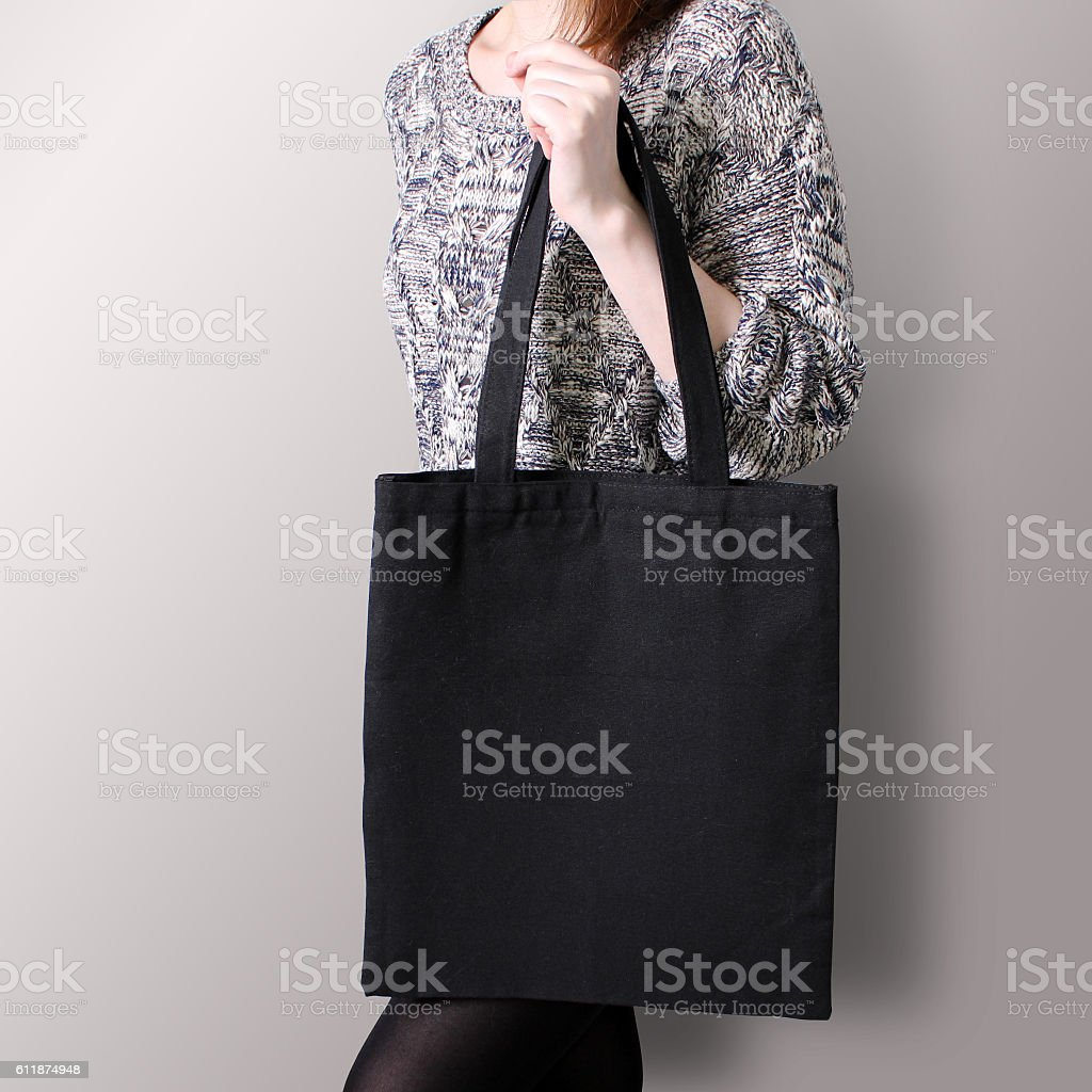 Mock-up. Girl is holding black cotton tote bag. stock photo