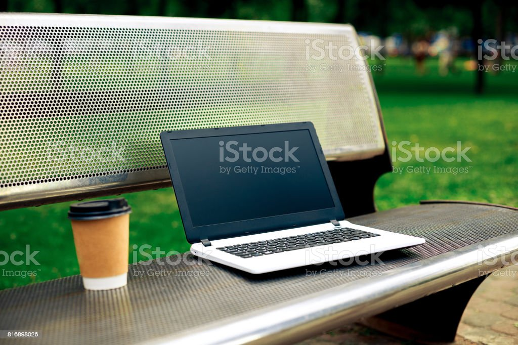 Mockup image of laptop with blank black screen and coffee cup on metal bench in nature outdoor park stock photo
