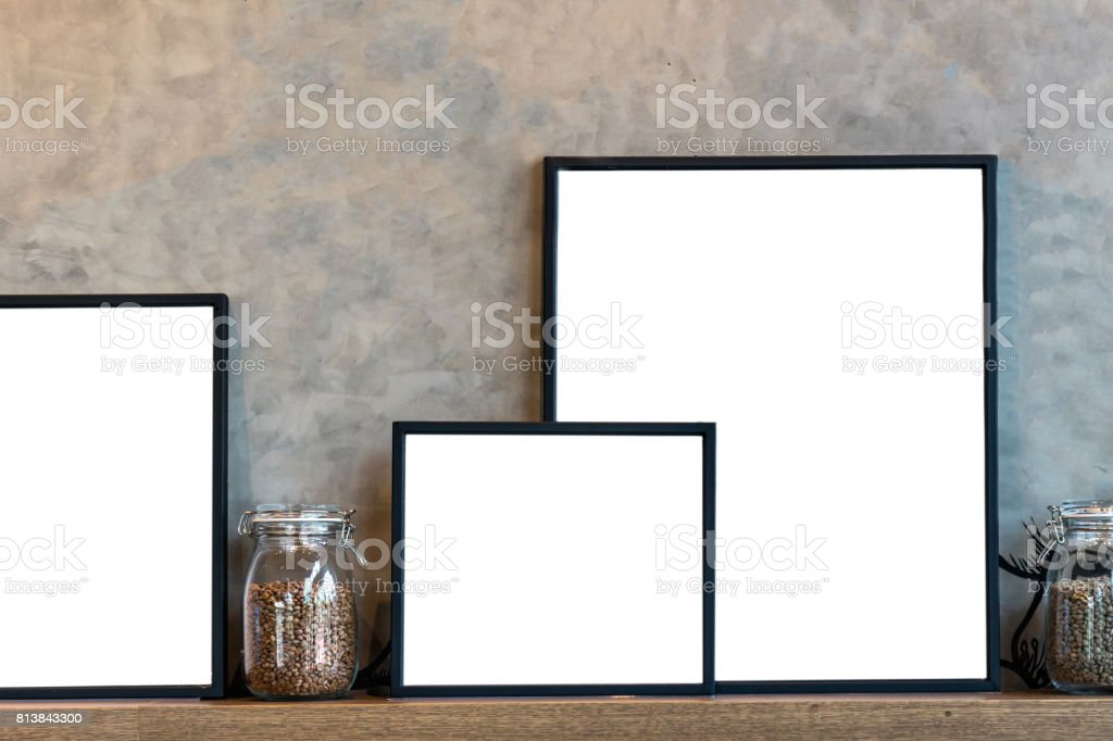 Mockup of photo frame and coffee in glass jar over the wooden shelves on Vintage wall background. Product presentation with interior concept stock photo