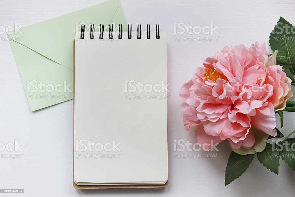 Mockup photography with pink peony, notebook and envelope stock photo