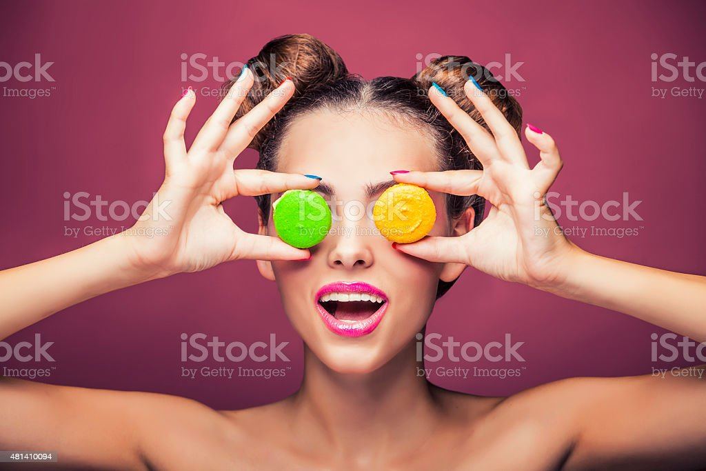Model, a woman with bright make-up and colour biscuits joking. stock photo