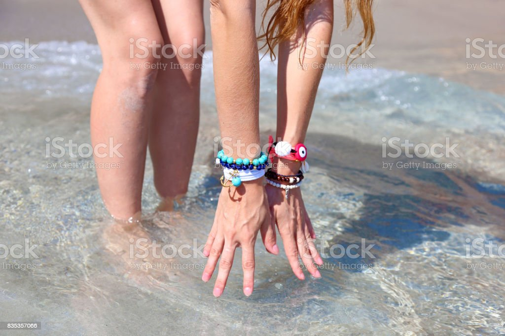 model advertises greek jewelry on the beach stock photo