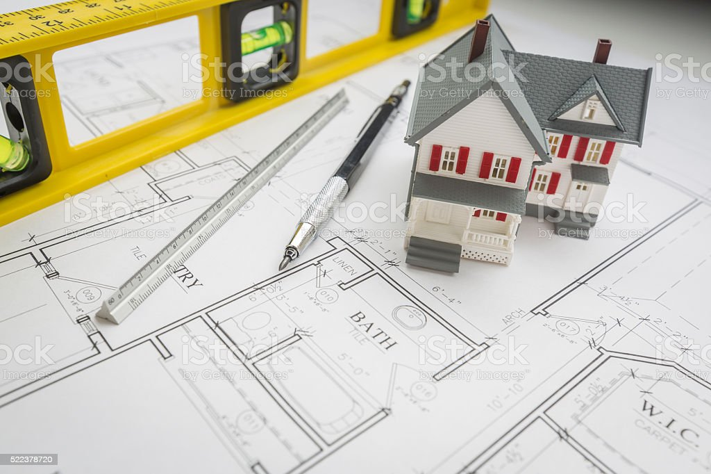 Model Home, Level, Pencil and Ruler Resting on House Plans stock photo