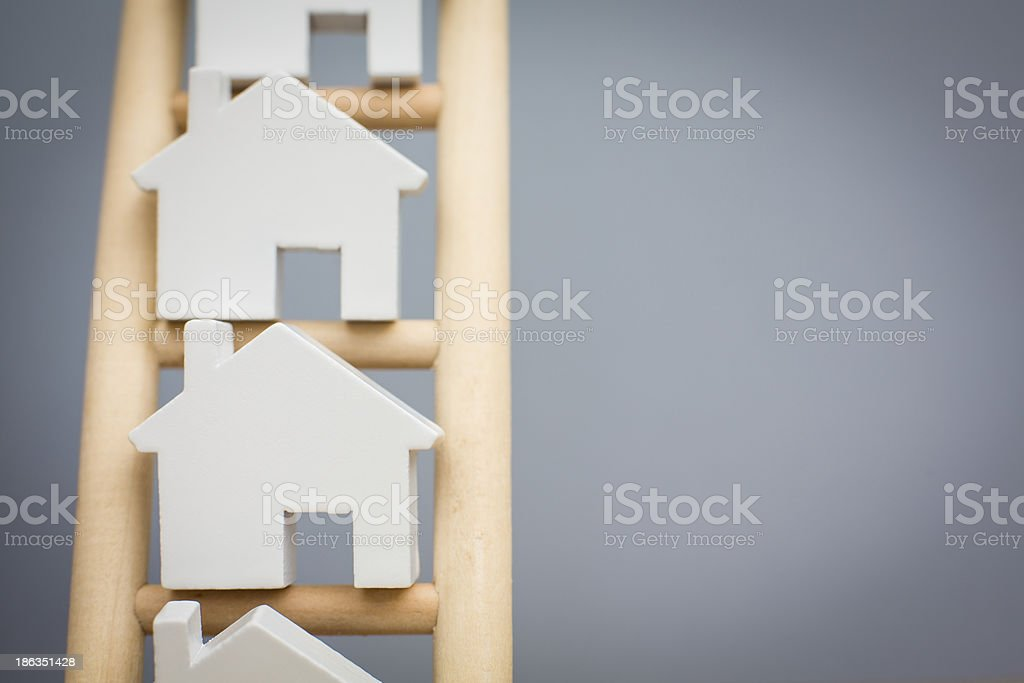 Model house icons on a wooden property ladder royalty-free stock photo