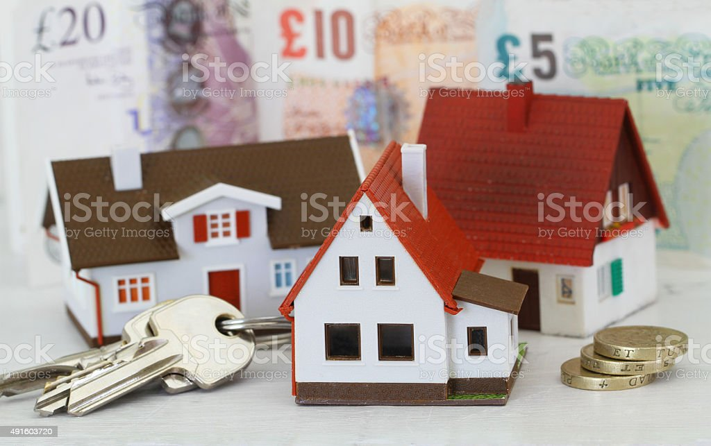 Model houses and keys with British Pounds in the background stock photo