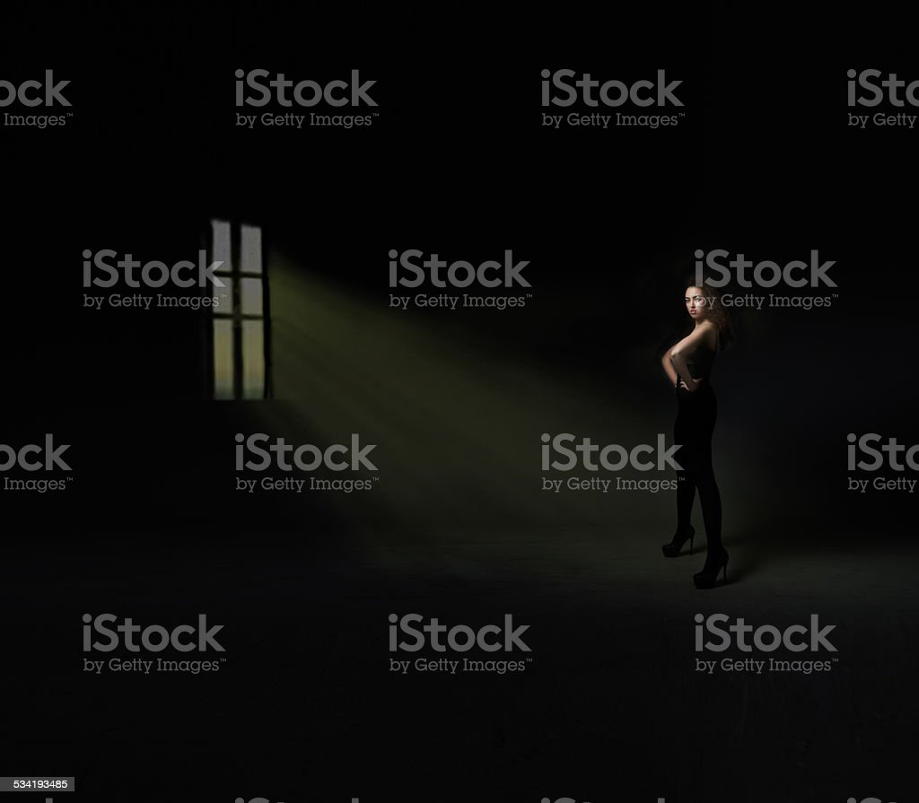model in front of windon on a dark room stock photo