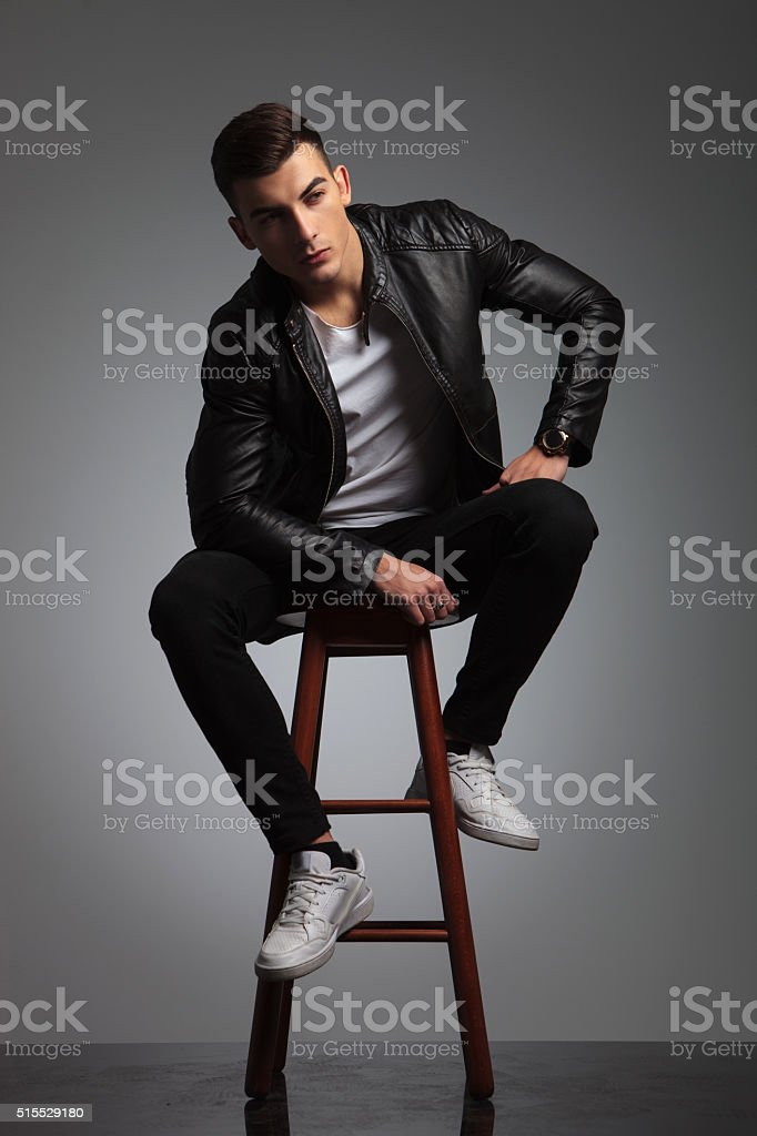 model in leather jacket posing seated in studio while resting stock photo