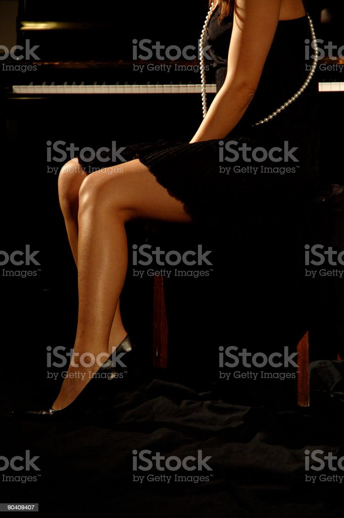 Model legs with piano stock photo