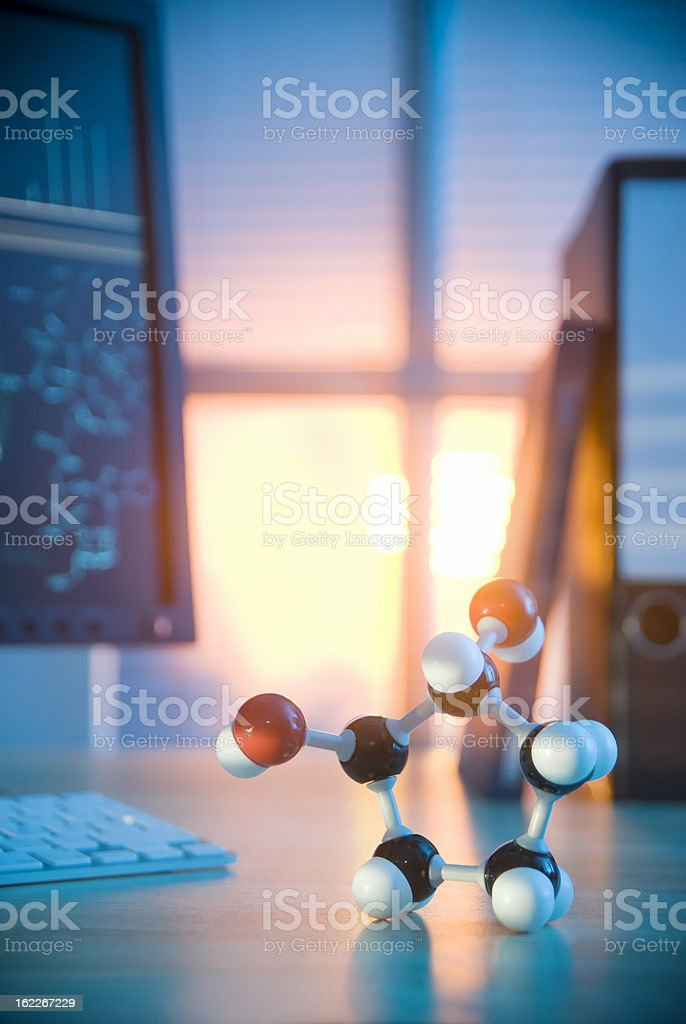 Model of a molecule on a desk in front of computer royalty-free stock photo