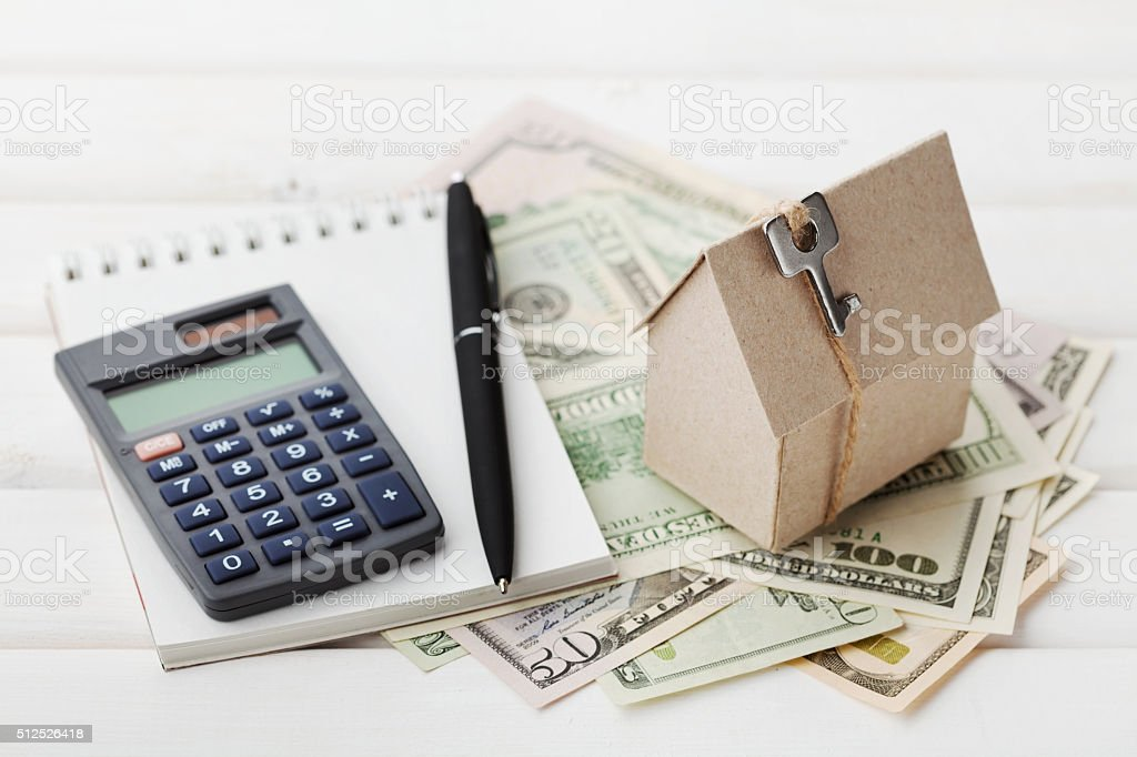 Model of cardboard house, calculator, notebook, pen and cash dollars stock photo