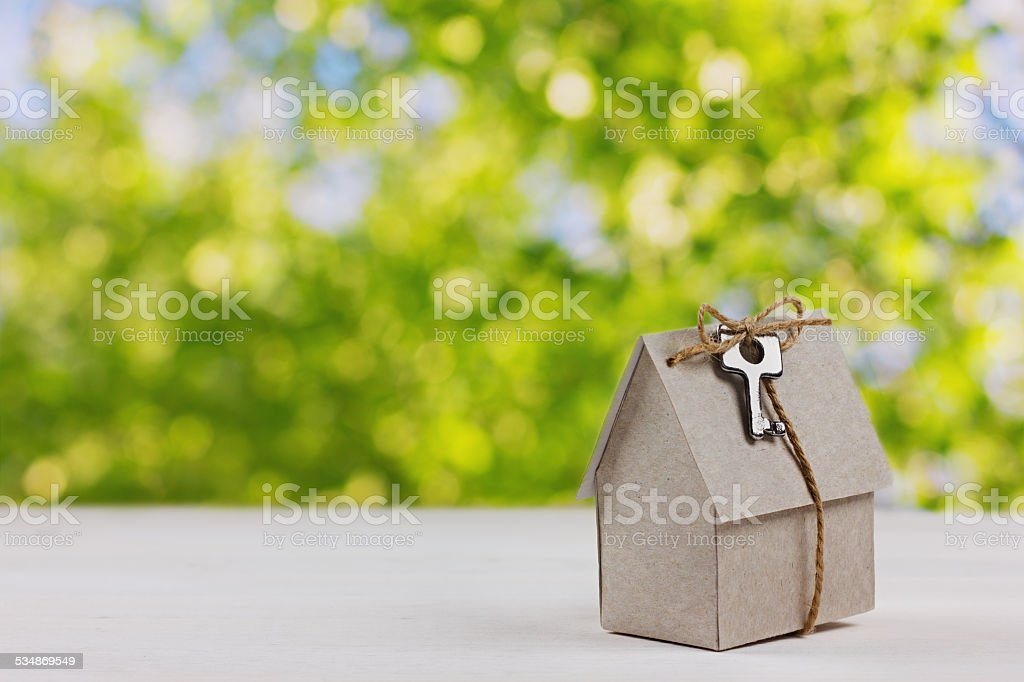 model of cardboard house with key against green bokeh background stock photo