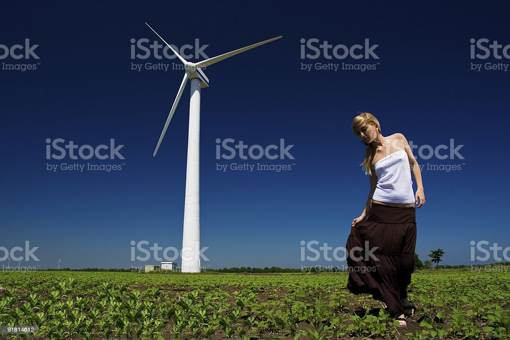 Model posing in front of wind power generator royalty-free stock photo
