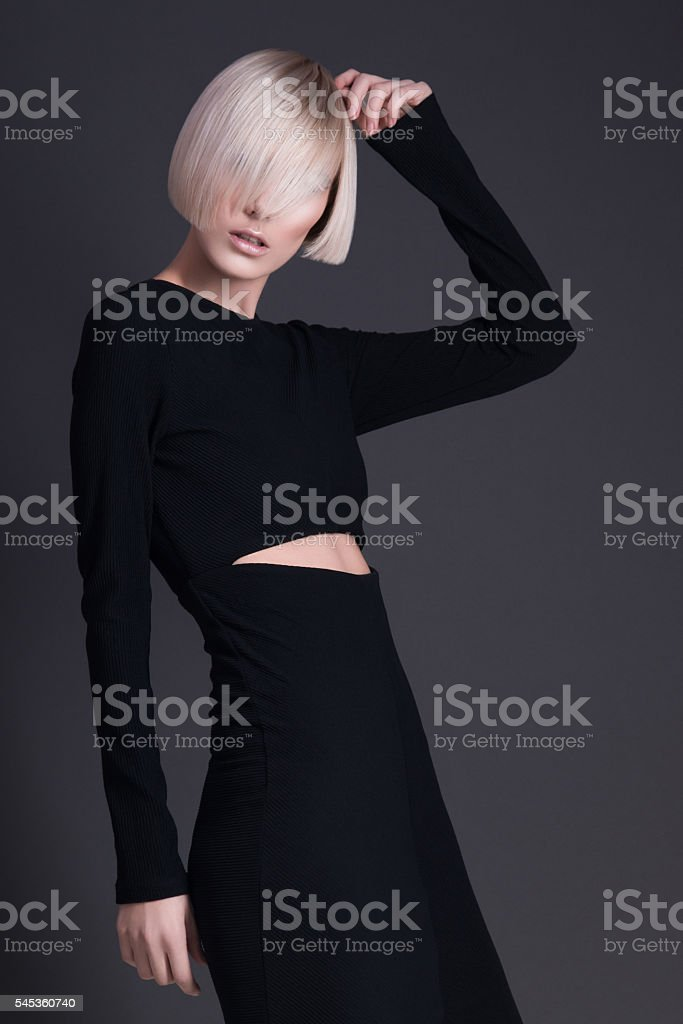 Model posing looking in camera. Strong angry girl, dark grey stock photo