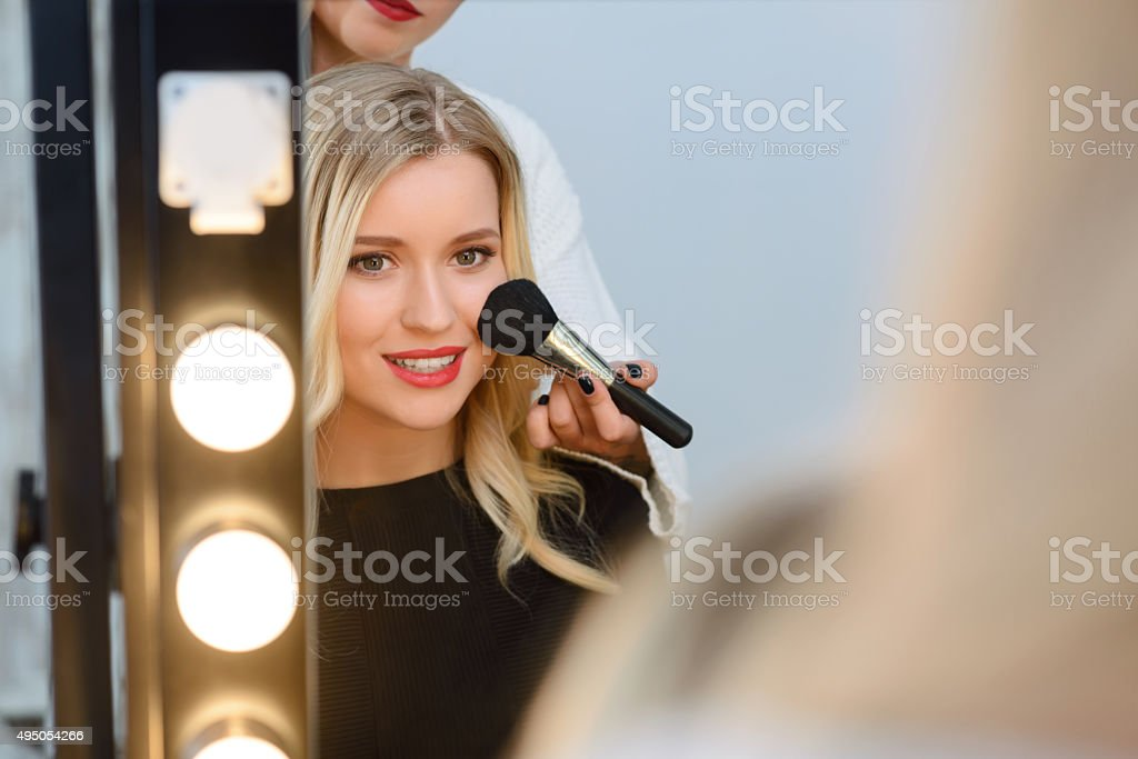 Model sitting in front of mirror while applying blush stock photo