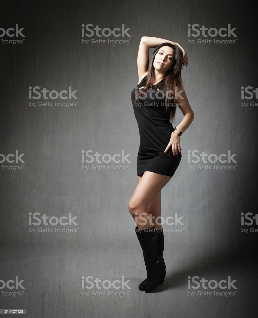 model standing with a mini dress in gray background stock photo