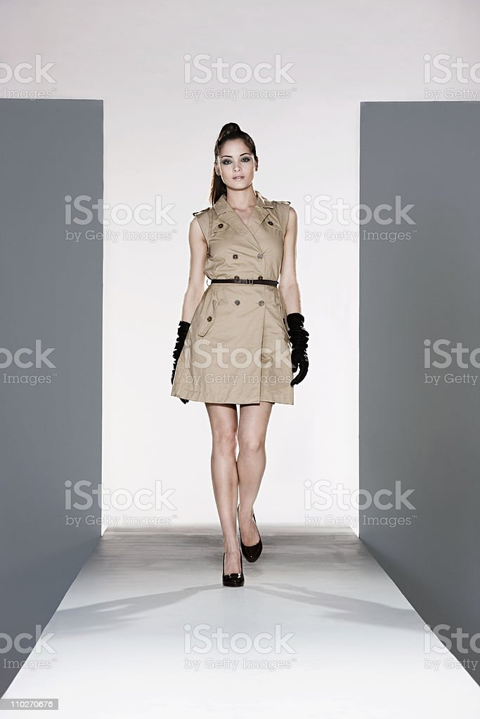 Model wearing beige dress on catwalk at fashion show stock photo