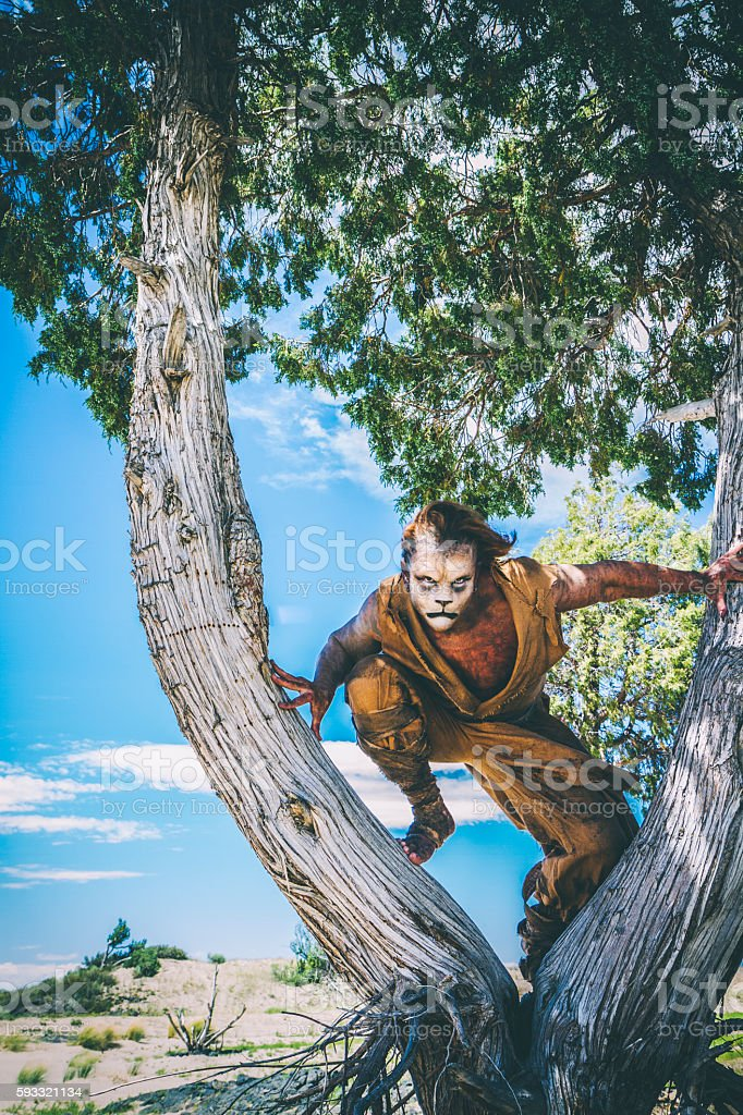 Model Wearing Lion Makeup & Costume  Leaping From A Tree stock photo