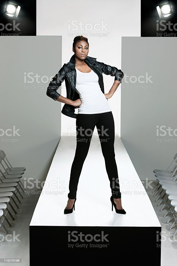 Model with black leather jacket on catwalk at fashion show stock photo