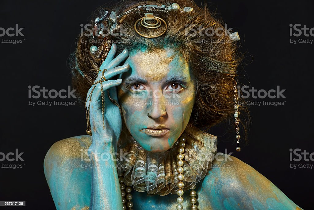 Model with gold and green body art. stock photo