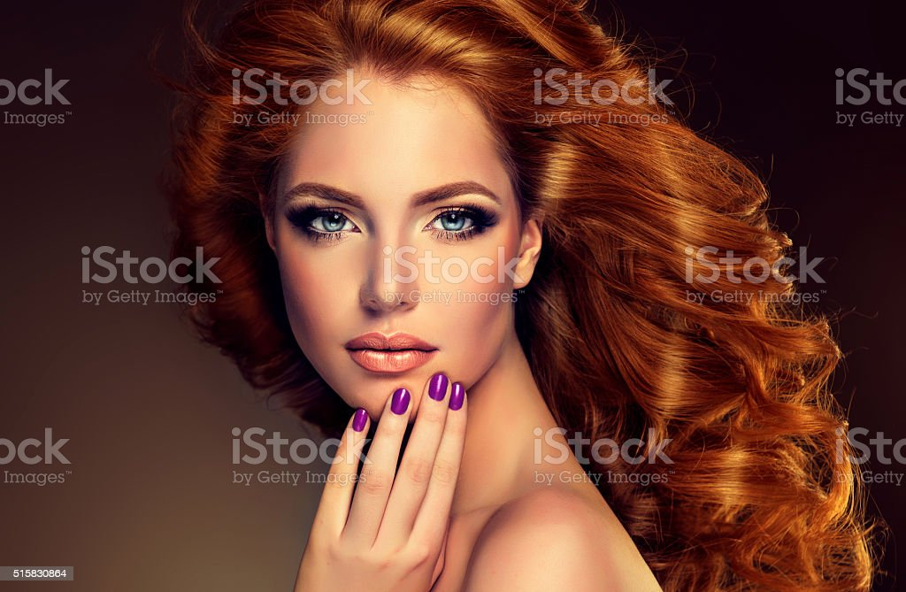 Model with long curly red hair and purple nails. stock photo