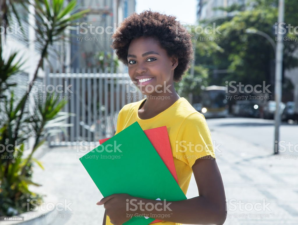Modern african american female student in a yellow shirt stock photo