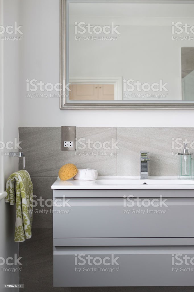 A modern and clean bathroom sink, mirror, sponge and towel stock photo